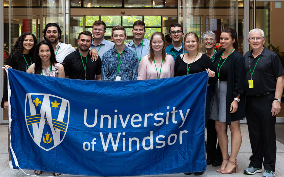 Students holding uwindsor flag