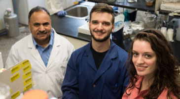 Students and faculty smiling in the lab